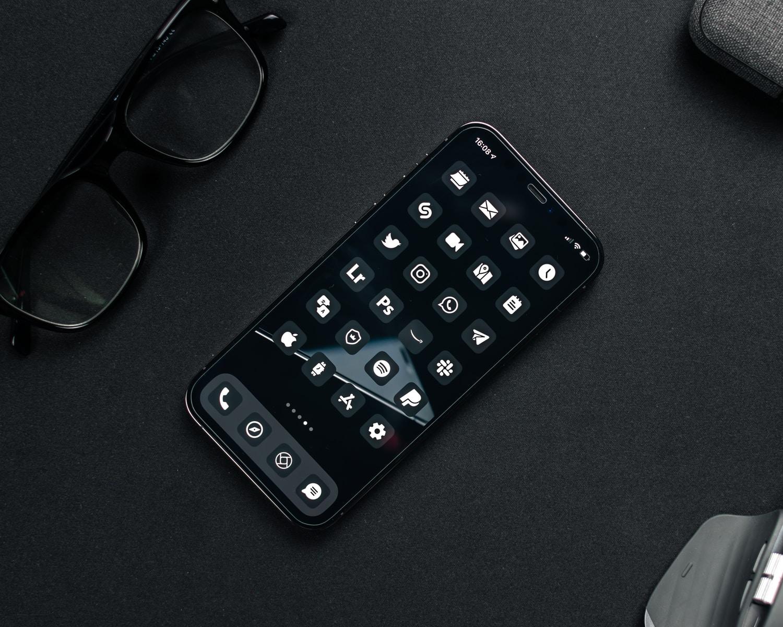 black remote control beside black framed eyeglasses